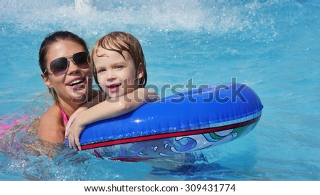 a small child with his mother in the pool - stock photo