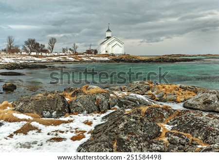 A small Church with a cemetery stands on the shore of the fjord - Lofoten islands, Norway - stock photo