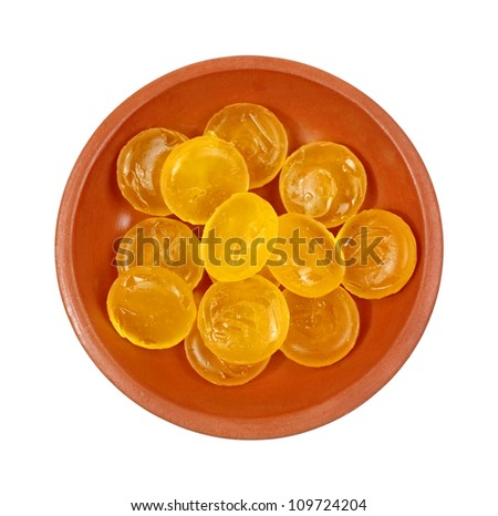 A small clay dish of honey and lemon cough drops.