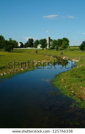 A small clear farm brook winds it's way past fertile farm land and an Amish farm and homestead - stock photo