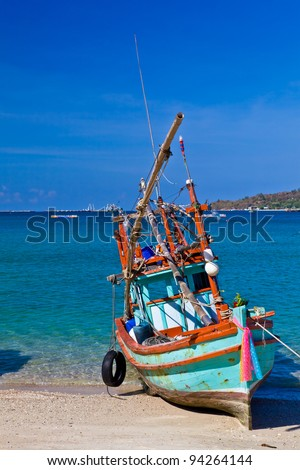 A small colorful wooden fishing boat is run aground on the beach with the background of blue sea