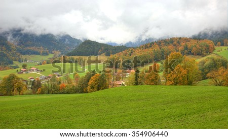 A small country village between green meadows and trees with farmhouse on a beautiful autumn hillside in Ramsau Bavaria Germany(deep vivid version) - stock photo