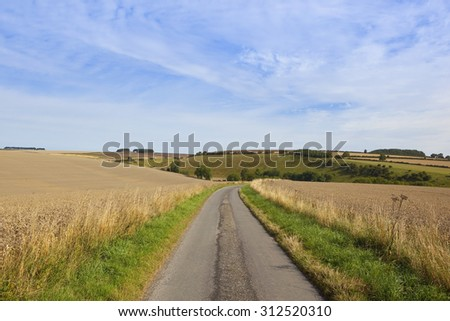 a small countryside road on the yorkshire wolds england with views of patchwork farmland under a blue sky in late summer