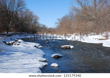A small creek after a fresh snowfall in winter - stock photo