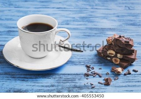 A small cup of strong black espresso coffee, slices of chocolate bars with hazelnuts on a blue wooden background surface - stock photo