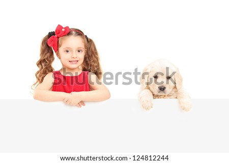A small cute girl and labrador retriever posing behind a blank panel isolated on white background - stock photo
