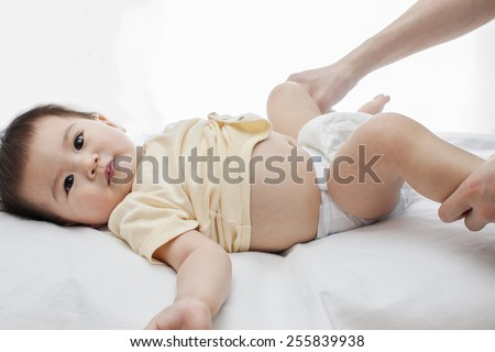 A small cute little baby girl was lying down, her diaper was being changed by her father, closeup, white background, studio - stock photo