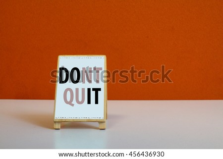 A Small cute wooden Sign or menu stand with orange background and word Dont Quit