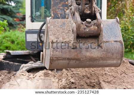 A small digger is making the hole on the bulding site. - stock photo