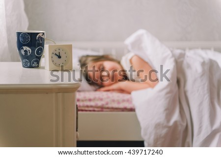 A small diseased girl in the bedroom. Little girl sitting on a bed wearing a pajamas. girl is sick. girl measures the temperature. She feels bad. Sick little girl lying in the bed with thermometer