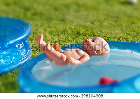 a small doll floating in the plastic pool - stock photo