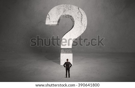 A small elegant business person in suit standing with his back in front of a huge question mark in open space concept - stock photo
