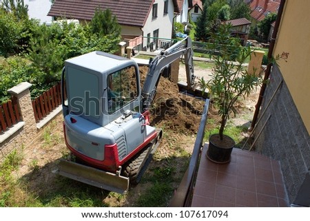 a small excavator provides garden at the house - stock photo