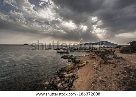 A small fish boat in a small natural port, located in Karpathos island Greece, faces Kasos island and a cloudy, dramatic sky during sunset. - stock photo