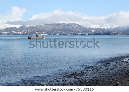 A small fishing boat heading out to sea in the Kachekmak Bay in Alaska - stock photo