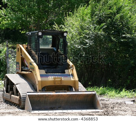 A small front end loader working a load of gravel - stock photo