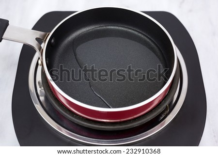 A small frying pan with olive oil heating on a single burner stove element. - stock photo