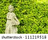 A small garden statue in a garden on a city front yard. - stock photo
