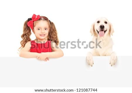 A small girl and Labrador retriever posing behind a blank panel - stock photo