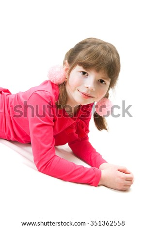 A small girl is lying on floor on white background