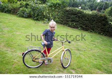 A small girl learning to ride a bike.