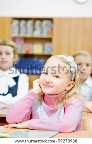 A small girl sits at the desk - stock photo