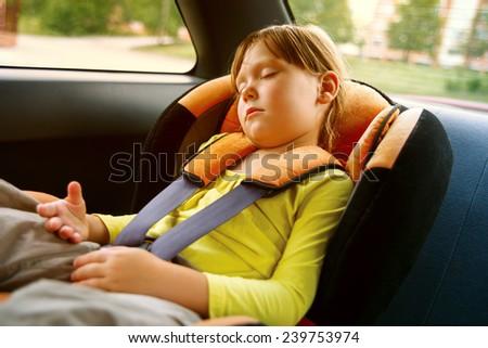 a small girl sleeps in car - stock photo