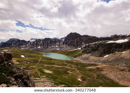 A small glacier-fed lake surrounded by an alpine meadow and snow-capped mountains in the Canadian rockies. - stock photo