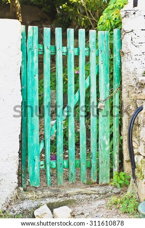 A small green wooden gate at the edge of a garden - stock photo