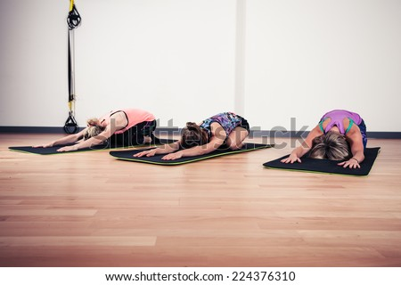 A small group of women are practicing yoga in a gym - stock photo