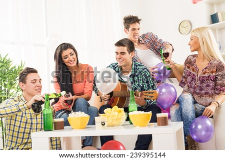 A small group of young people at the home party, enjoy the sounds of the acoustic guitar, drinking wine and beer. - stock photo