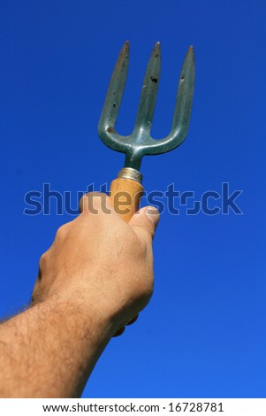 A small hand held garden fork held aloft against a bright clear blue sky background. - stock photo