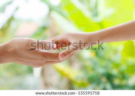 A small hand put in bigger hand with love and care