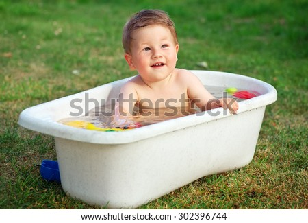A small happy baby bathed in the bath and playing in a bath with toys.  - stock photo