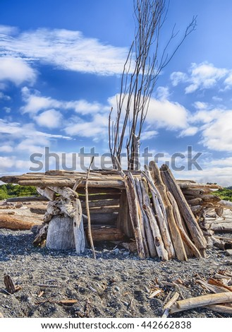A small homemade structure with an entrance, built out of driftwood on a beach in Puget Sound, provides shelter from the wind.