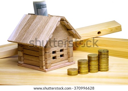 A small house standing at building materials and coins. Credit for the construction of wooden house in the mountains. Buying a new home. Isolated on white background. - stock photo
