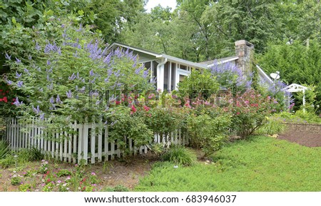 A small house surrounded by many colorful bushes and flowers.