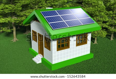a small house with white walls and green roof has some solar panels placed on one side of the roof with the sun that reflects in them, on a grassy ground and trees behind it - stock photo