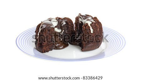 A small individual sized lava cake that has been cut in half to show the filling on a blue striped plate.
