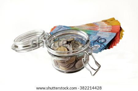 A small jar containing Australian coins with banknotes behind, all shown on a white background which gives space for your text - stock photo