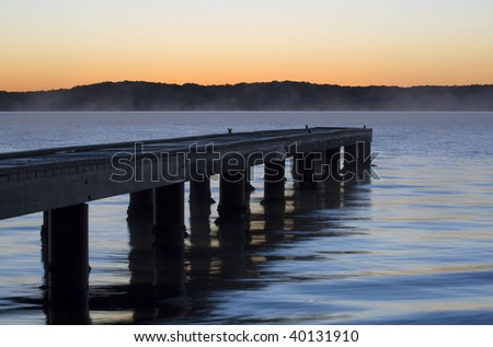 A small jetty jutting out onto the lake at sunrise
