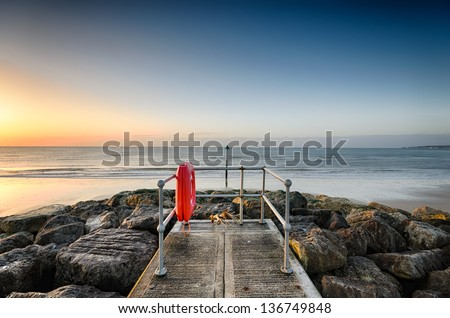 A small jetty on the beach at Sandbanks in Poole, Dorset looking out towards Old Harry Rocks - stock photo