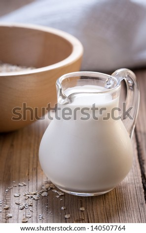 A small jug of milk on wooden background - stock photo