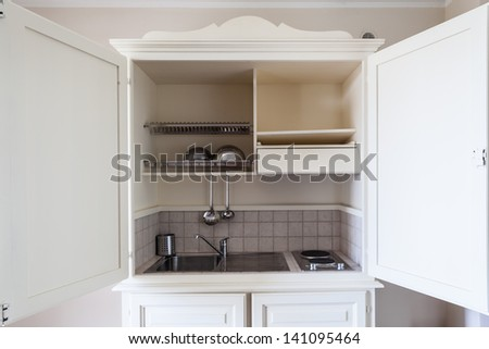 a small kitchen contained inside a wood cabinet - stock photo