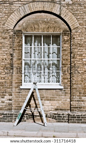 A small ladder in front of the window of a town house in England - stock photo