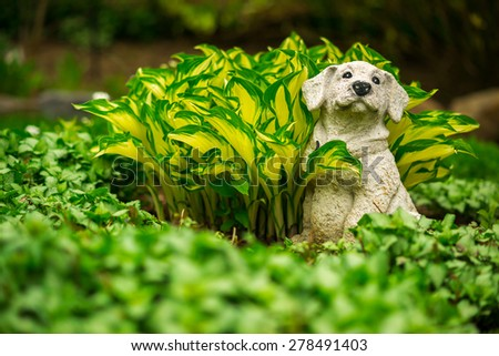 A small lawn ornament statue of a cute and happy small dog sits looking content amongst the lush greenery of a fertile garden.