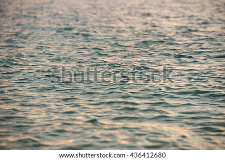 a small light ripples in the water green hue with reflection sunset - stock photo