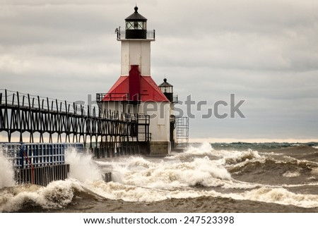 A small lighthouse out on a pier in St. Joesph Michigan during stormy weather with waves crashing into the pier. - stock photo