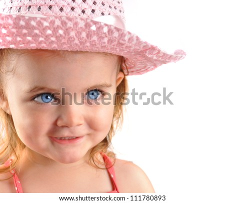 A small little girl is looking off to a blank white background. The child is wearing a pink hat and is happy with blue eyes.