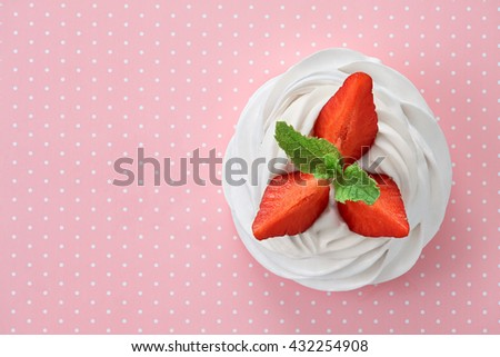 A small meringue Pavlova dessert with some strawberry slices garnished with mint leaves on a pink dotted background. Top view, all in focus. - stock photo